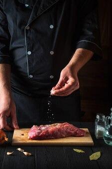 요리사는 생 쇠고기 고기에 소금을 뿌립니다. 굽기 전에 고기를 준비합니다. 레스토랑이나 카페의 주방에서 일하는 환경