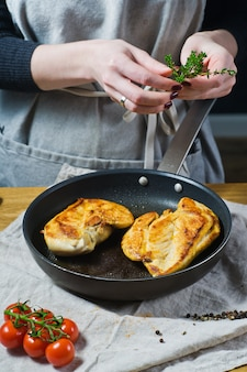 Chef sprinkles thyme on chicken breasts in a frying pan.