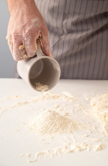 Chef sprinkling flour on the working surface