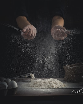 Chef sprinkling flour