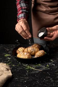 Chef sprinkling salt over potatoes in pan