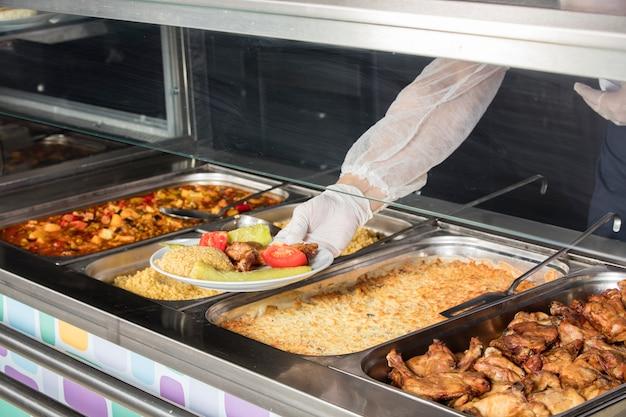 Шеф-повар стоит за станцией обслуживания обедов Premium Фотографии