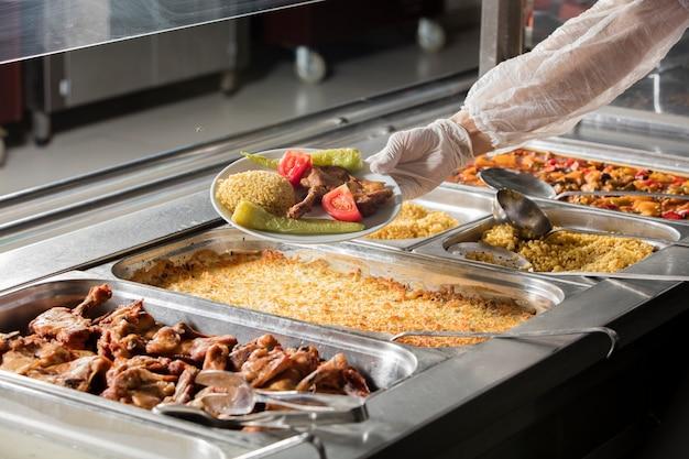 Шеф-повар стоит за станцией обслуживания обедов