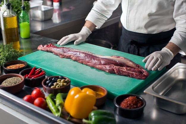 Шеф-повар, стоя на кухне, готовит стейк из говядины