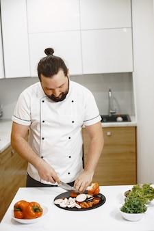 Chef in piedi in cucina a casa, cucina