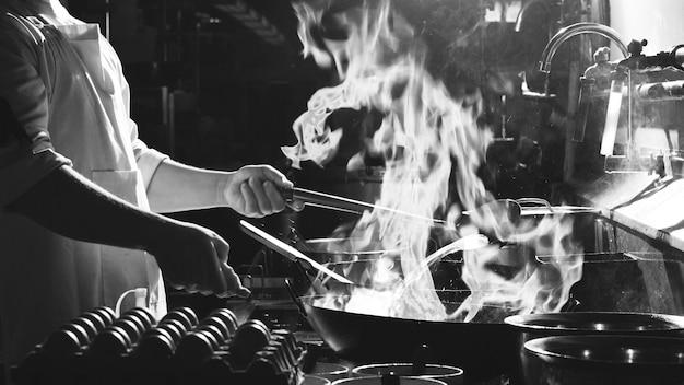 Шеф-повар жаркое движения занят приготовлением пищи на кухне. шеф-повар обжаривает продукты на сковороде, коптит и разбрызгивает соус на кухне. монохромный фильтр
