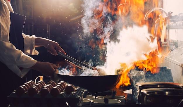 シェフがキッチンで忙しい料理を炒めます。シェフはフライパンで食べ物を炒め、燻製し、キッチンでソースをはねかけます。