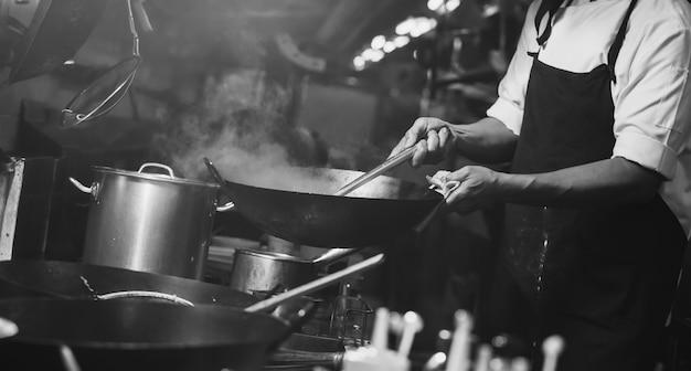 Шеф-повар жаркое движения занят приготовлением пищи на кухне. шеф-повар обжаривает продукты на сковороде, коптит и разбрызгивает соус на кухне.