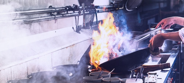Chef stir fry cooking in kitchen