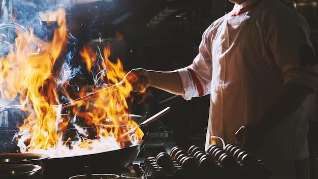 냄비에 요리사 볶음 튀김