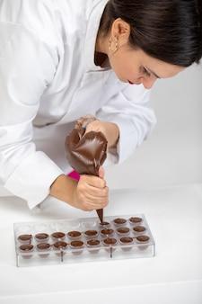 シェフがかき混ぜて、暗く溶かしたチョコレートをプラスチックの型に注ぎます