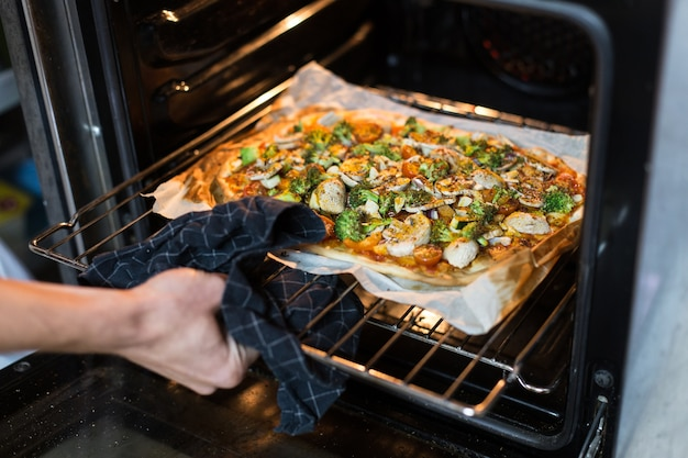 Chef takes out homemade organic wholewheat pizza from oven, uses table cloth not to burn hand
