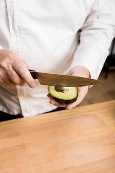 Шеф-повар вынимает семена авокадо