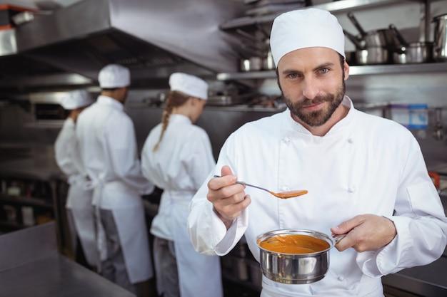 レストランのキッチンでスプーンから食べ物を味わうシェフ