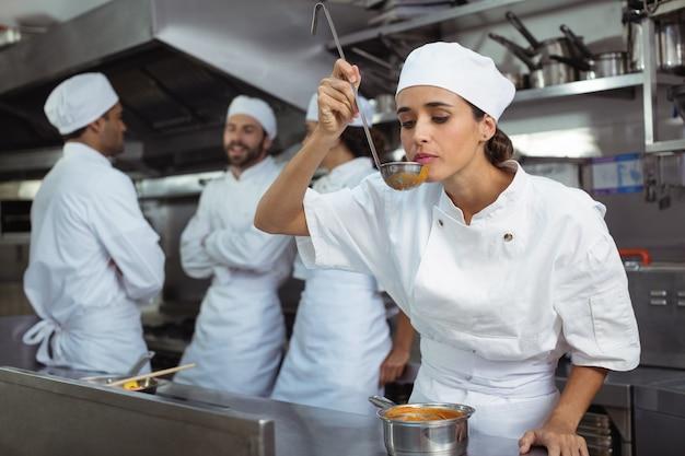 シェフがキッチンでスプーンから食べ物を味わう