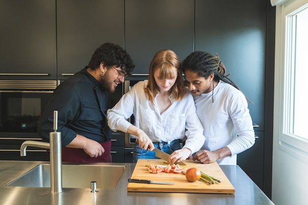 Chef teaching mixed race couple how to cook.