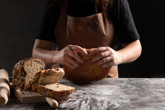 焼きたてのパンを引き裂くシェフ