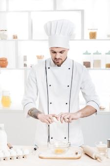 Chef in uniform breaks eggs in a bowl to prepare dough in the kitchen