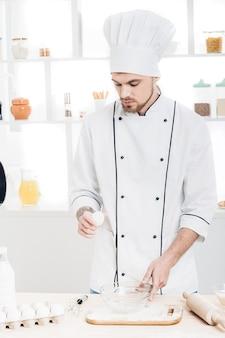 Chef in uniform breakseggs in bowl to prepare dough in kitchen