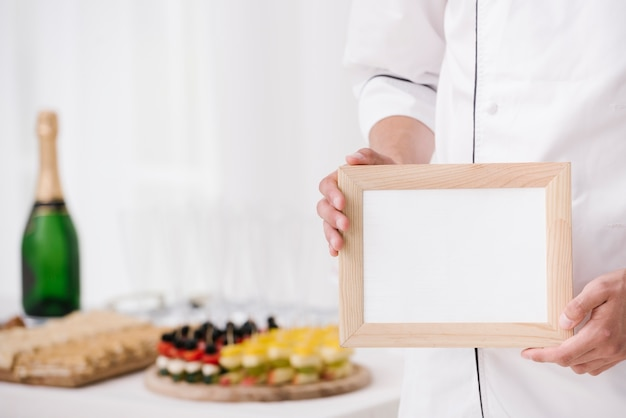 Chef in uniform holding wooden frame with mock-up