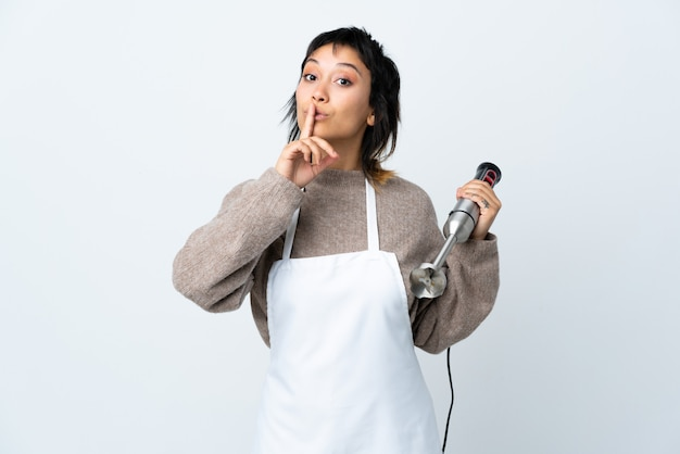 Chef uruguayan girl using hand blender over isolated white doing silence gesture