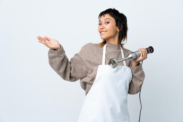 와서 초대 측면에 손을 연장 격리 된 흰 벽에 손 믹서기를 사용하여 요리사 uruguayan 소녀