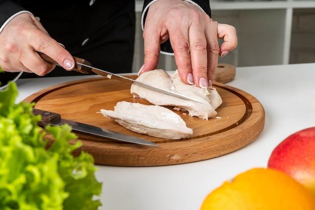 Шеф-повар, используя разделочную доску и нож