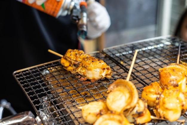 일본 가리비와 조개에 화염 토치를 사용하는 요리사