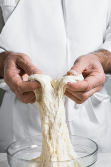 Chef in white clothes making dough for bread front view