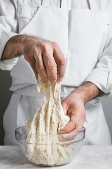 Chef in white clothes making dough