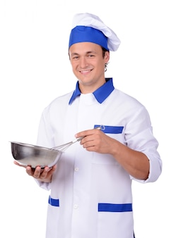 Chef in white uniform and hat with kitchen pan.