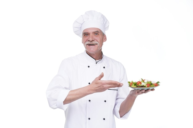 Chef in white uniform holds vegetable salad.