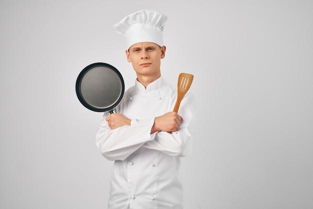 手にフライパンを持ったシェフ、台所用品レストランの料理。高品質の写真