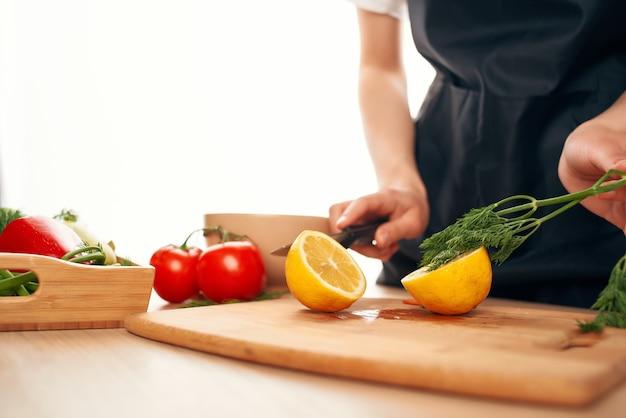 손에 칼을 든 요리사는 야채와 레몬 부엌 가정 요리를 자른다