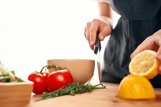 手にナイフを持ったシェフが野菜とレモンキッチンの家庭料理をカットします