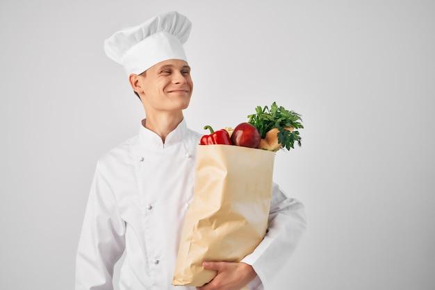Шеф-повар с пакетом продуктов на кухне готовит пищу. фото высокого качества