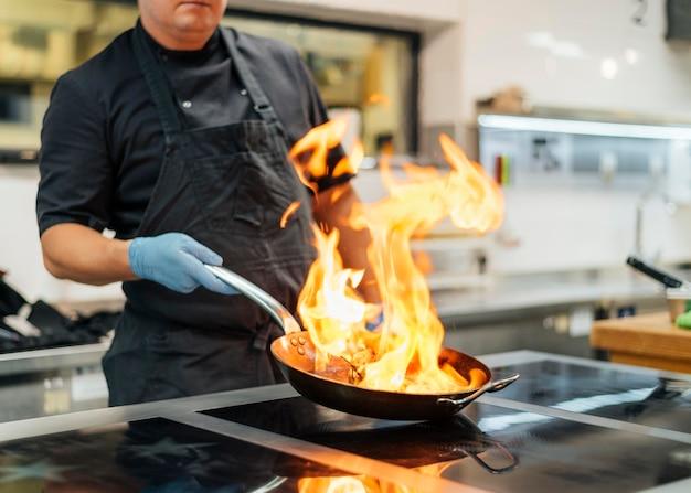 エプロンと手袋のフランベ料理を持つシェフ