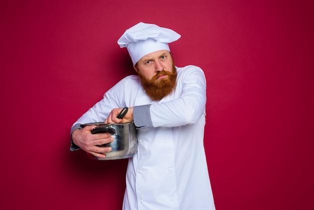 턱수염과 빨간 앞치마를 가진 요리사는 그의 조리법을 질투합니다.