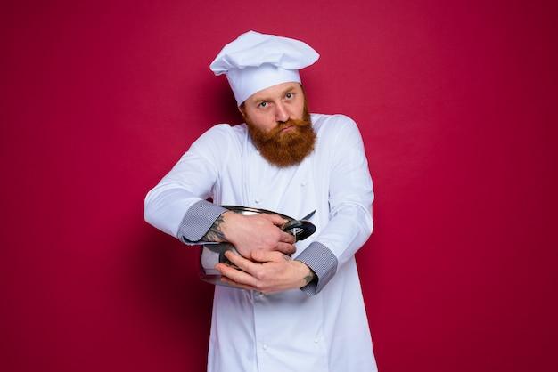 수염과 빨간 앞치마를 한 요리사는 그의 요리법을 질투합니다