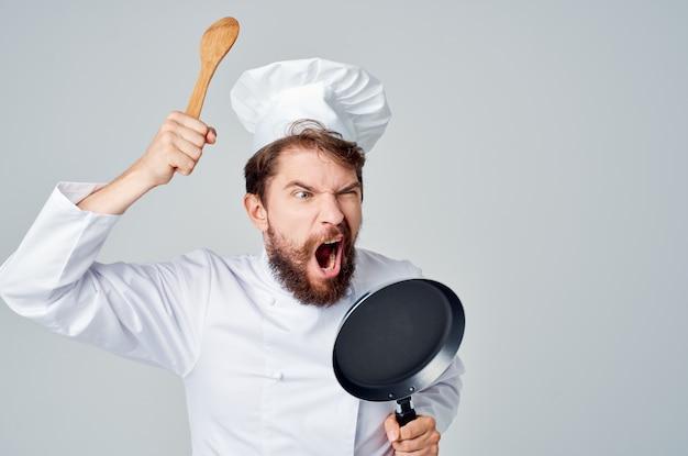 Повар с кухонной утварью ресторан профессионально готовит. фото высокого качества