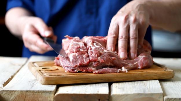 A chef with a knife cuts a raw pork neck. raw pork on a cutting board.