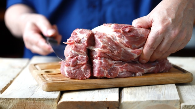A chef with a knife cuts a raw pork neck.