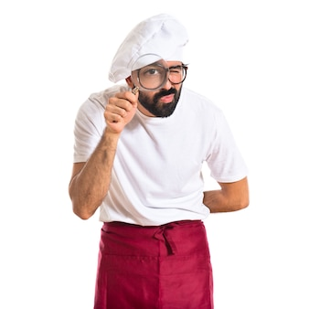 Chef with magnifying glass over white background