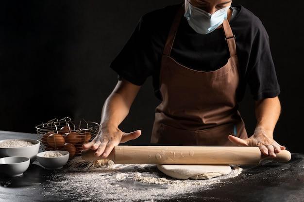 Шеф-повар с медицинской маской раскатывает тесто на столе