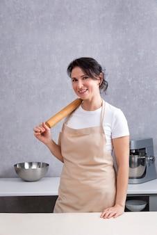그녀의 어깨에 롤링 핀과 카메라에 미소를 가진 요리사. 수직 프레임.