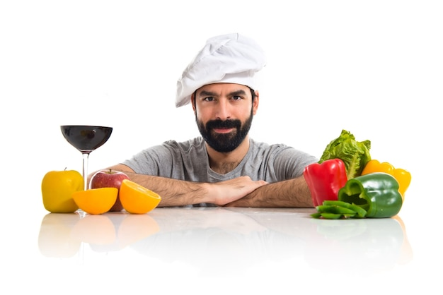 Шеф-повар с несколькими овощами и фруктами на столе