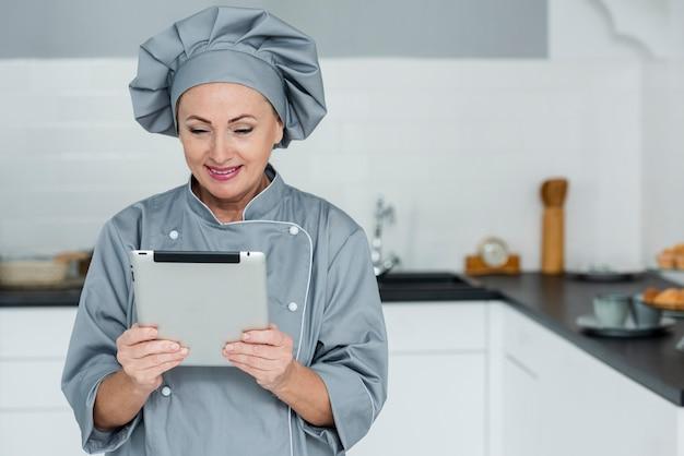 Chef con tavoletta in cucina