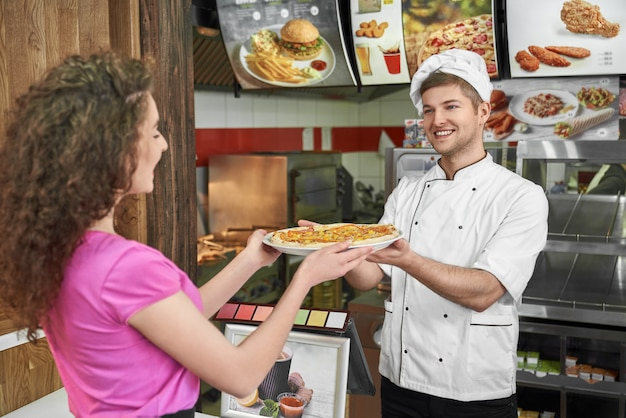 Chef working in pizzeria and proposing pizza to pretty girl.