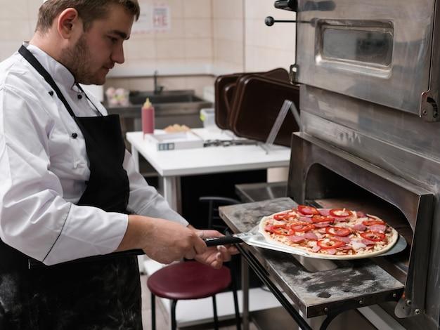 Cheff는 피자를 요리하고 오븐에 넣어 굽습니다. 프리미엄 사진