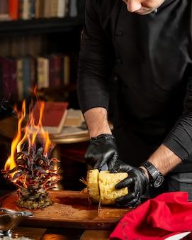 Cheff tagliando l'ananas a fette accanto alla cima frondosa che brucia